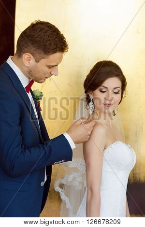 Young wedding couple enjoying romantic moments indoors against gold yellow background