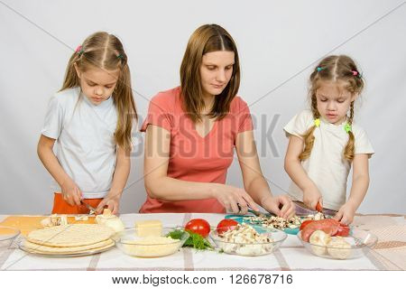 Mom Teaches Two Daughters To Cook. It Helps Them To Cut Mushrooms And Vegetables