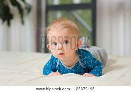 Baby boy lying on belly. Cute year-old kid with interest looks at the camera, boy lying on bed in the bedroom with white linens. Home interior in the background.