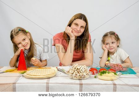 Satisfied Mother With Two Daughters Sitting Resting His Head In His Hands At The Table With The Prod