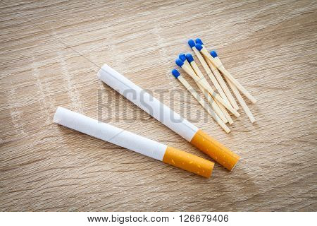 cigarettes and matches on a woody background
