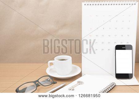 coffee and phone with keyeyeglassesnotepadcalendar on wood table background