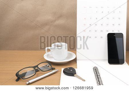 coffee and phone with car keyeyeglassesnotepadcalendar on wood background