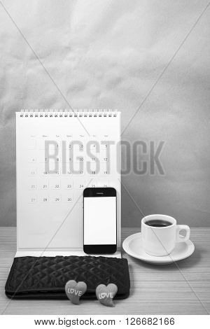 office desk : coffee with phone calendar wallet heart on wood background black and white tone