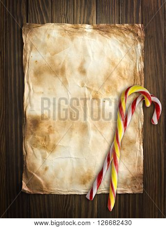 Old paper on wooden background with Christmas candy.