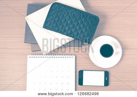 working table : coffee with phonestack of book and wallet on wood background vintage style
