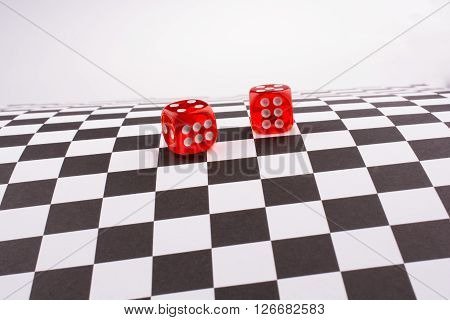 Red dice with white dots on a checked background