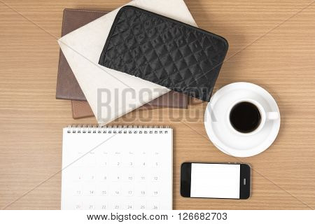 working table : coffee with phonestack of book and wallet on wood background