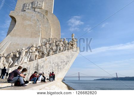 LISBON PORTUGAL - FEBRUARY 02 2016: People sitting by the Monument to the Discoveries and enjoying the view
