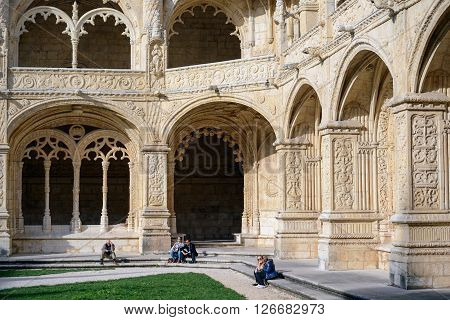 LISBON PORTUGAL - FEBRUARY 02 2016: People sitting in the cloister of the Jeronimos Monastery a monastery of the Order of Saint Jerome located near the shore of the parish of Belem Lisbon Portugal.