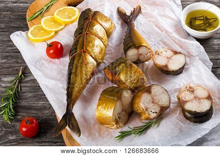 Slices of Smoked fish Mackerel or Scomber on a white parchment paper with cherry tomato sliced lemon and rosemary on an old wooden table with small bowl with olive oil studio ligths top view