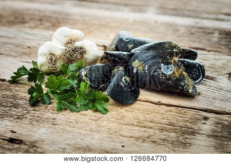 Raw Mussels Garlic And Parsley On Old Wooden Table