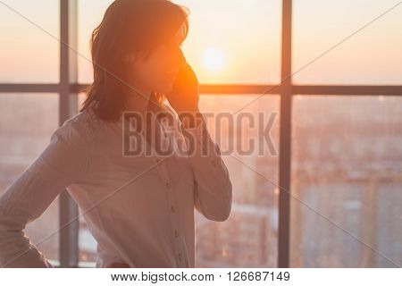 Young woman busy with calling, chatting on the cell phone side view portrait. Close-up picture of a businesswoman holding mobile device at her workplace