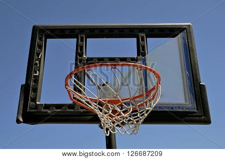 The plexiglass of a backboard is broken on an outdoor basketball court.