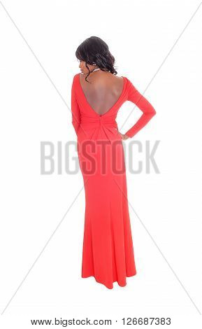 A lovely slim African American woman in a long red dress and curly long black hair standing from the back isolated for white background.