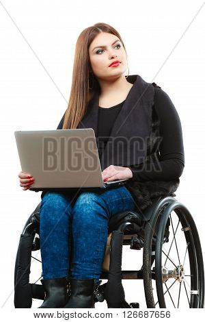 Real people disability and handicap concept. Teen girl unrecognizable person sitting on wheelchair using laptop computer networking studio shot on white
