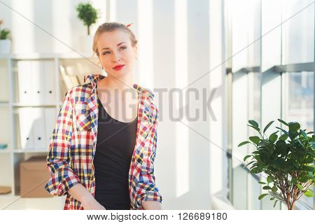Thoughtful young woman sitting at a light room in the morning, bowed her shoulder, dreaming. Relaxed female blonde girl looking aside, front view portrait