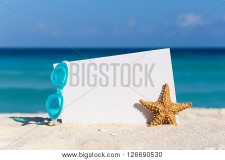 Blank White Board, Swimming Glasses And Starfish On Sand Against Turquoise Caribbean Sea Water