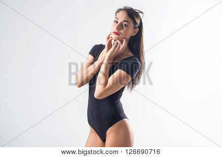 Brunette fit female standing in studio, touching her chin with fingers, wearing black swimwear, keeping sunglasses on the head, not isolated