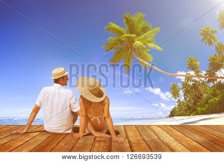 Couple Sitting on Wooden Floor at Beach