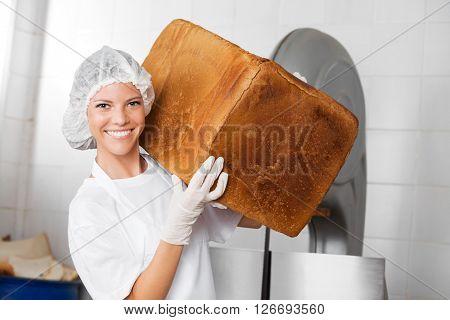 Smiling Female Baker Carrying Big Bread Loaf