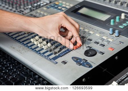 Professional's Hand Working On Audio Mixer In Studio