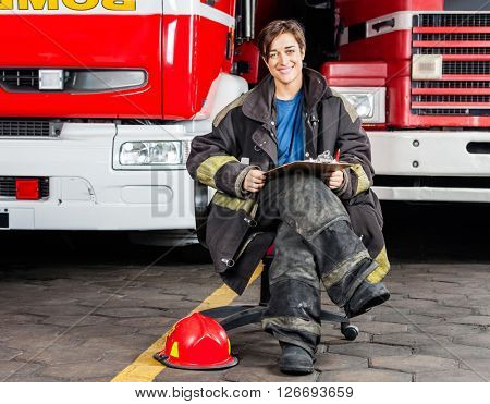Smiling Firewoman Sitting On Chair Against Trucks