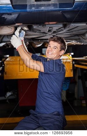 Happy Mechanic Working Underneath Lifted Car