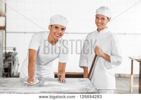 Smiling Female Baker's In Uniform Cleaning Bakery