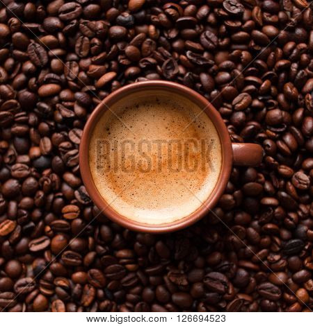 Coffee espresso cup on beans background. Top view