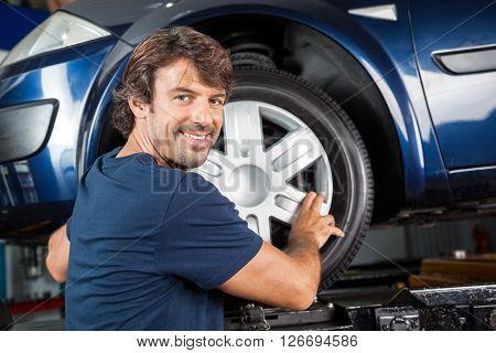 Confident Mechanic Fixing Alloy To Tire