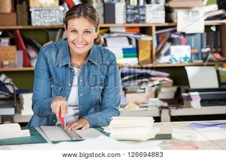 Happy Female Worker Cutting Paper At Table