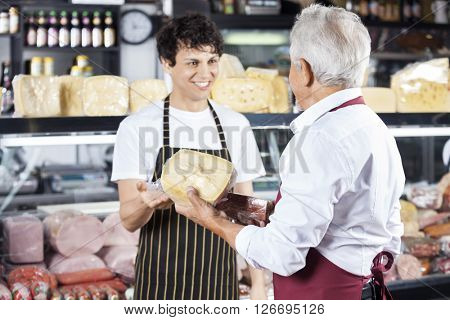 Salesman Receiving Cheese From Colleague In Shop