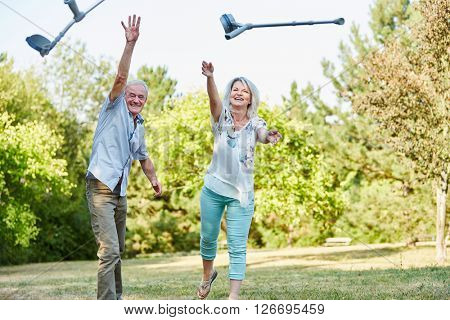 Senior couple in the park playfully throws crutches in the air