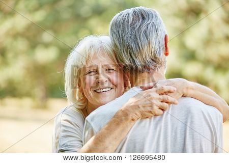 Happy woman hugs a man in the nature in summer