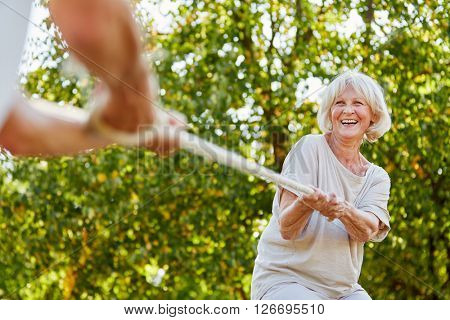 Happy senior woman playing tug of war with her husband in summer