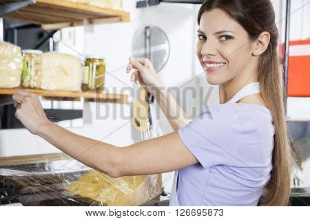 Smiling Saleswoman Packing Cheese At Grocery Store