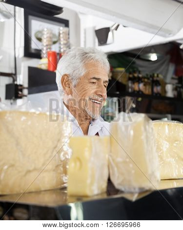 Salesman At Counter In Cheese Shop