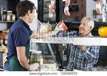 Salesman Selling Cheese To Senior Man