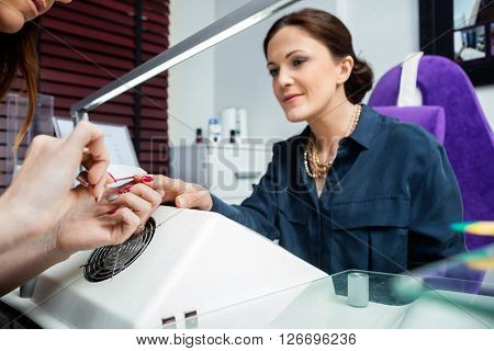 Cropped Image Of Manicurist Performing Manicure On Client's Hand