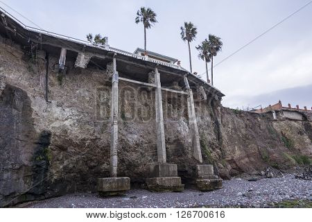 ROSARITO BAJA CALIFORNIA MEXICO - APRIL 7 2016: Eroding sea cliffs create a huge property insurance challenge for beachfront homes as concrete support systems only provide temporary stability.