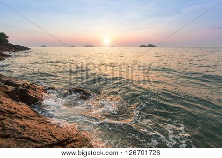 Surf at the rocky coast at sunset.