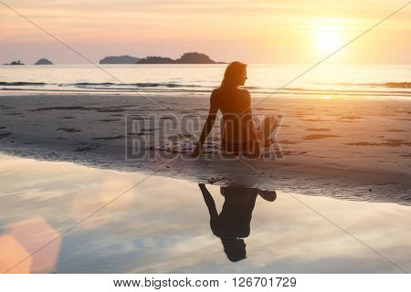 Beautiful young woman sitting on the beach in the setting sun. Silhouette, the reflection in the water.