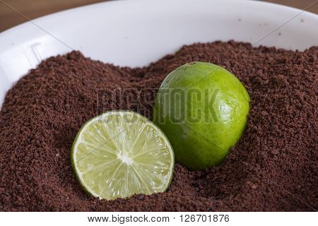 White bowl filled with freshly ground raw Theobroma cacao beans with one whole and one cut green lime