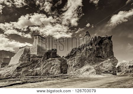 Ruins and Basgo Monastery surrounded with stones and rocks sky with clouds in the background Himalayan Mountain range Leh Ladakh Jammu and Kashmir India - tinted stock image of Indian monasteries
