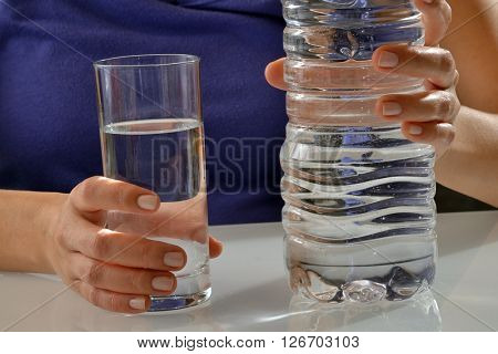Female hand holding glass and mineral water bottle.
