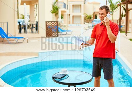 the tablet PC, phone and coffee on the table  near the pool - freelance or remote work concept. man talking by the phone near the pool.