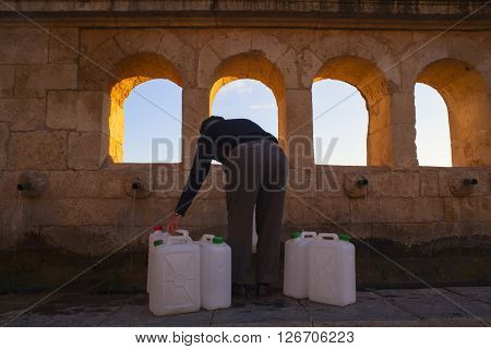 LEONFORTE ITALY - MARCH 25: Man filling cans with fountain water of the Granfonte baroque fountain in Leonforte on March 25 2016