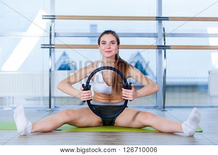 Pilates woman magic ring exercise workout at gym indoor.