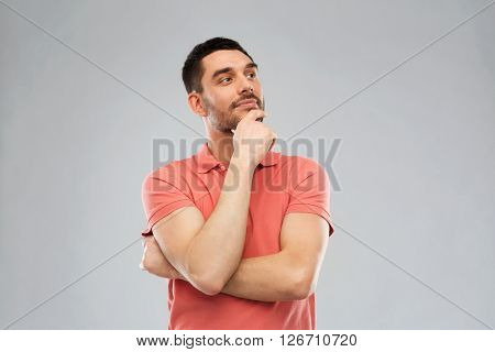 doubt, expression and people concept - man in polo t-shirt thinking over gray background